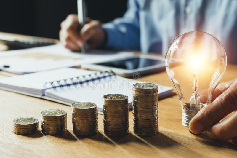 Business man holding light bulb on the desk in office and writing on note book it for financial,accounting,energy,idea concept. Business man holding light bulb stock image