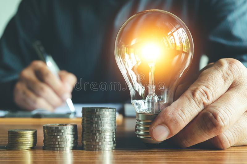 Business man holding light bulb on the desk in office and writing on note book it for financial,accounting,energy,idea concept. stock images