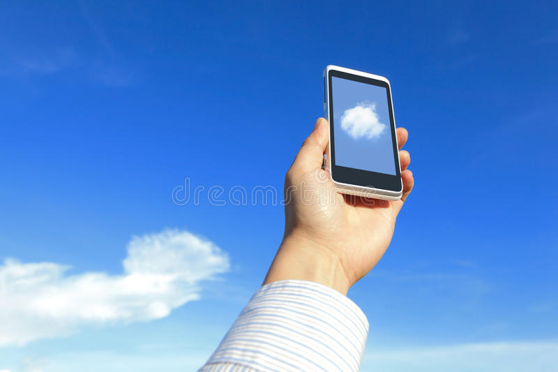 Business man holding mobile phone with cloud. Business man holding his mobile phone with white cloud and blue sky, concept for cloud computing stock images