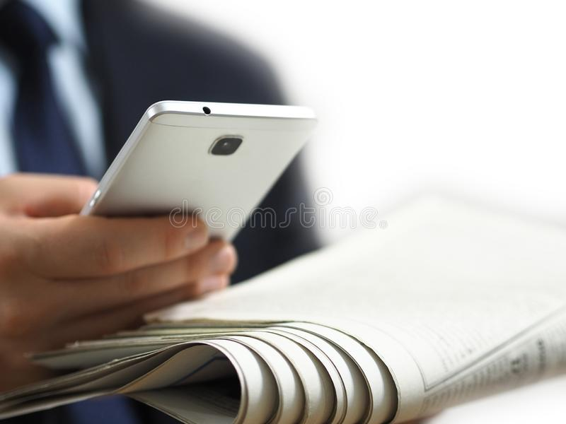 Business man holding a newspaper and a smart phone in his hand. The white background image stock image