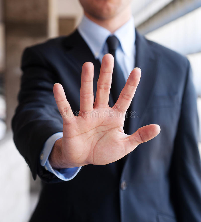 Business man holding out hand, indicating stop. Business man wearing a suit holding out hand in a gesture indicating stop royalty free stock photo