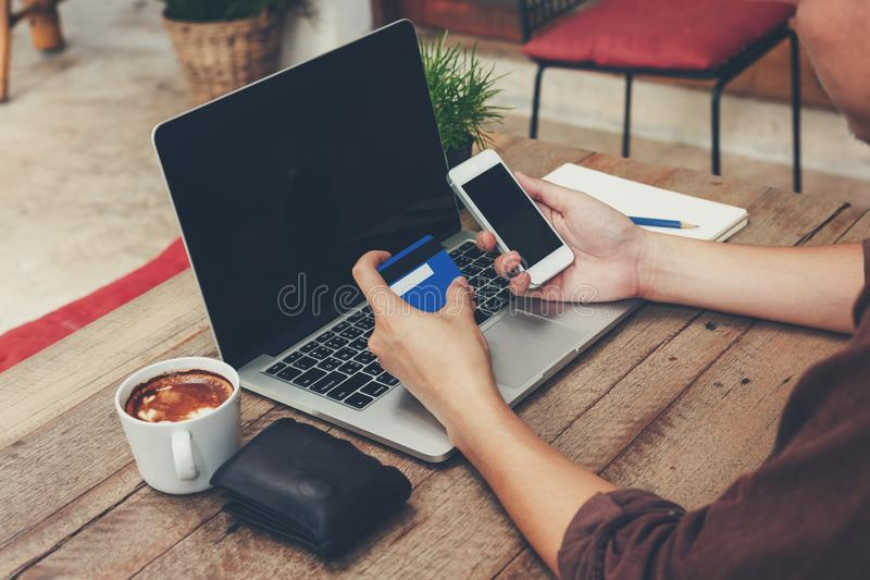 Business man holding phone and payment credit card with laptop o royalty free stock images