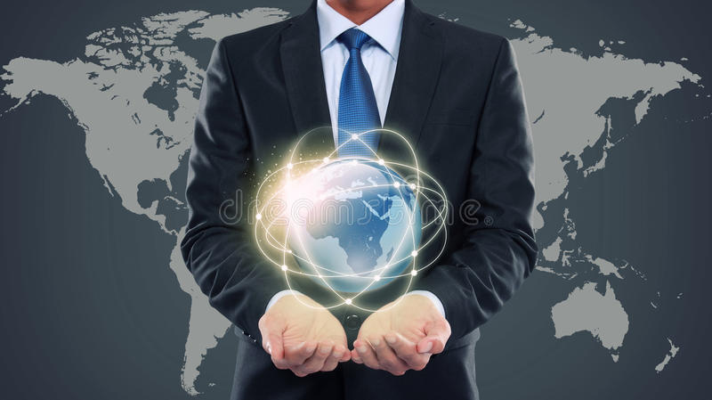 Business man holding the small world of multimedia. Business man holding the small world in his hands against world map background stock images