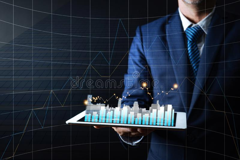Business man holding tablet with graph and building on dark background, finance and residence stock market concept royalty free stock photo