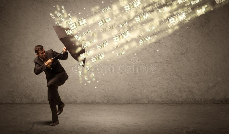 Business man holding umbrella against dollar rain concept. On grungy background stock photo
