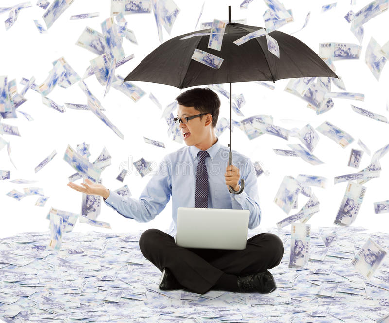 Business man holding a umbrella and catching money stock photo