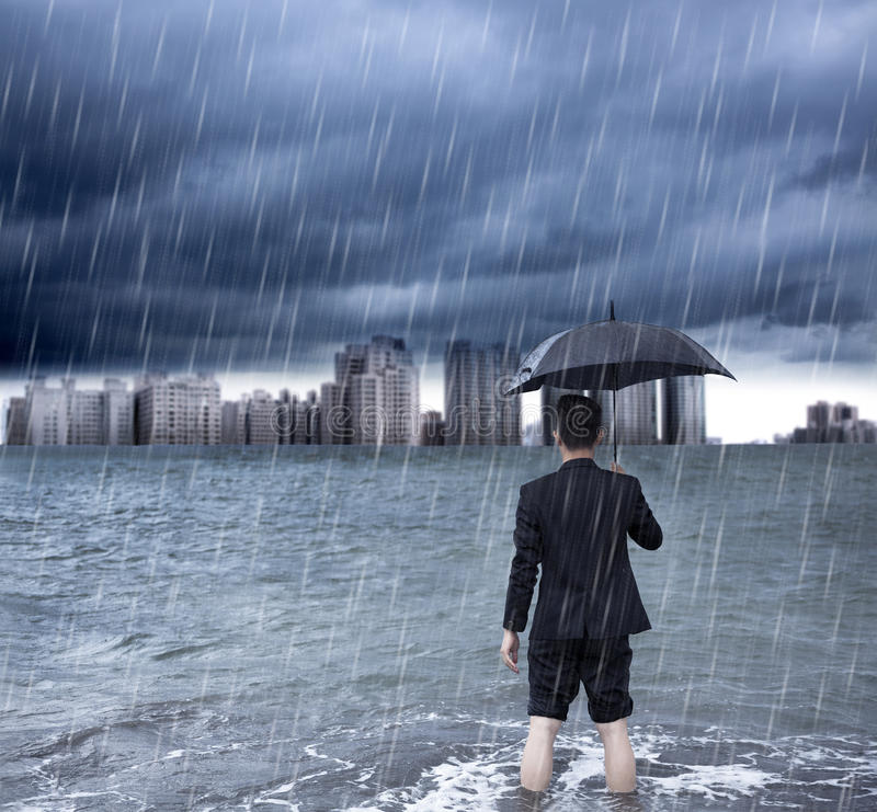 Business man holding an umbrella and standing with cloudburst. Background royalty free stock photography