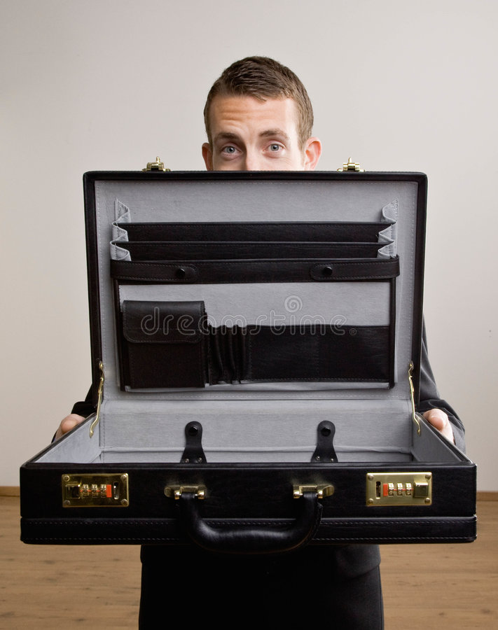 Business man holds up empty brief case royalty free stock photography