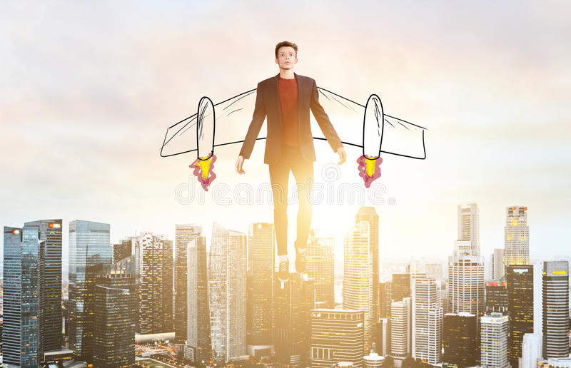 Business man hover over city skyline. Business Advantage. Businessman with sketch wings hovering over down town on sunset stock photo