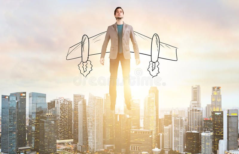 Business man hover over city skyline. Business Advantage. Businessman with sketch wings hovering over down town on sunset royalty free stock photo
