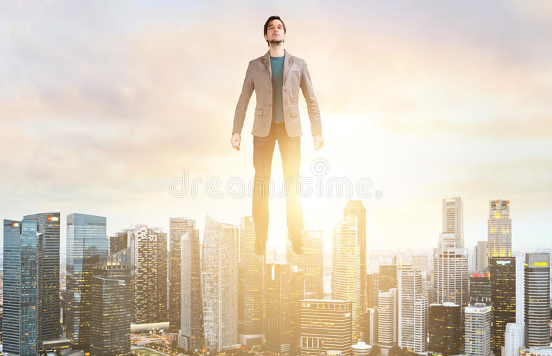 Business man hover over city skyline. Businessman hovering over down town on sunset royalty free stock photo