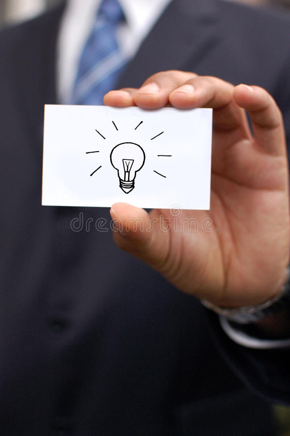 Business man with idea. Business man holding out a blank card in his hand with a drawing of a bulb idea concept royalty free stock photo