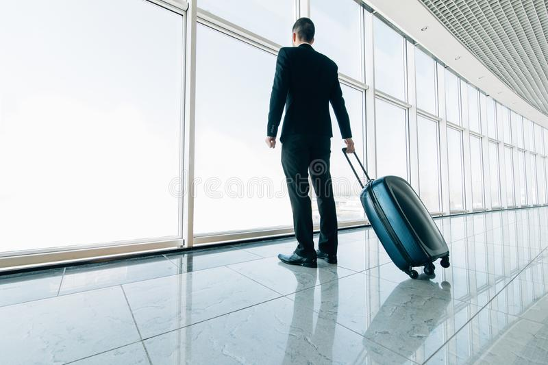 Business man at international airport moving to terminal gate for airplane travel trip. Mobility concept and aerospace industry fl stock photo