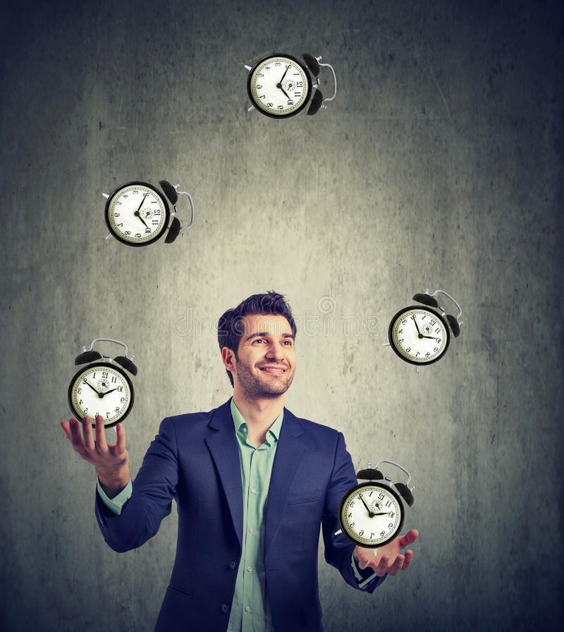 Business man juggling his time alarm clocks stock photos