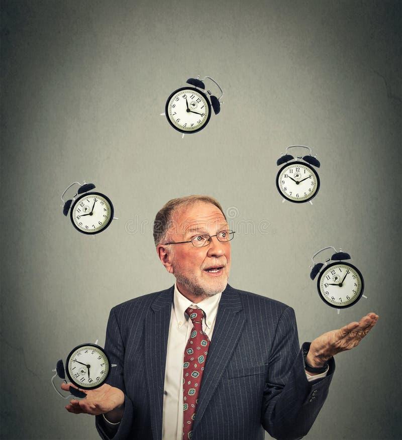 Business man juggling multiple alarm clocks stock photo