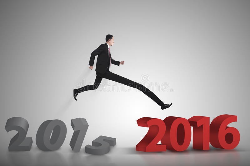 Business man jumping from 2015 to 2016 royalty free stock photography