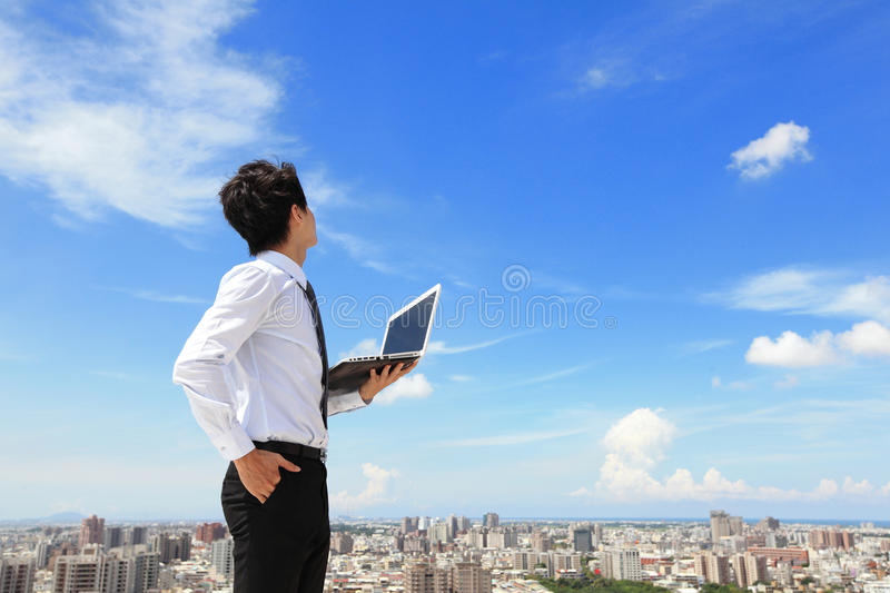 Business man with laptop and look sky and cloud stock photo