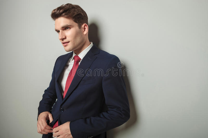 Business man leaning on a wall while closing his jacket. Portrait of a handsome business man leaning on a wall while closing his jacket stock photo