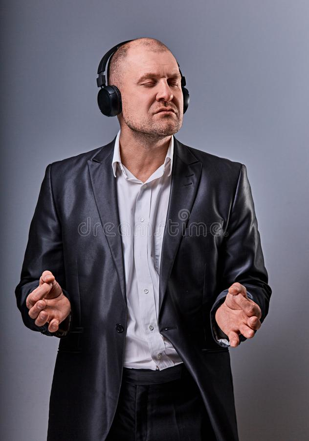 Business man listening the music in wireless earphone and trying relax he showing the hands yoga sign zen on grey studio royalty free stock photo