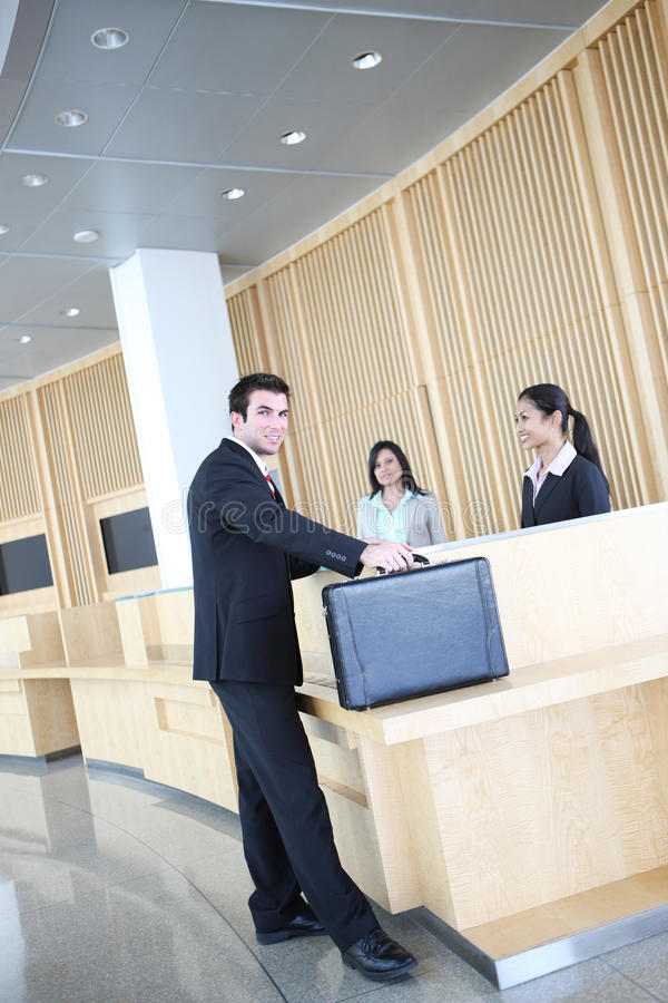 Business Man in Lobby. A handsome business man checking in with pretty women in company lobby royalty free stock photo