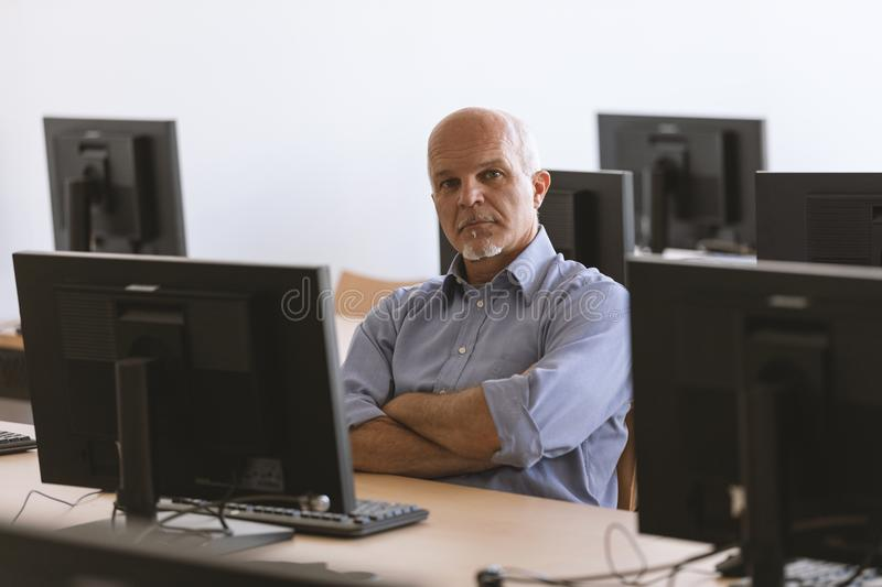 Man looking at camera with arms folded while sitting at desktop. Business man looking at camera with arms folded while sitting at desktop computer in classroom royalty free stock photos