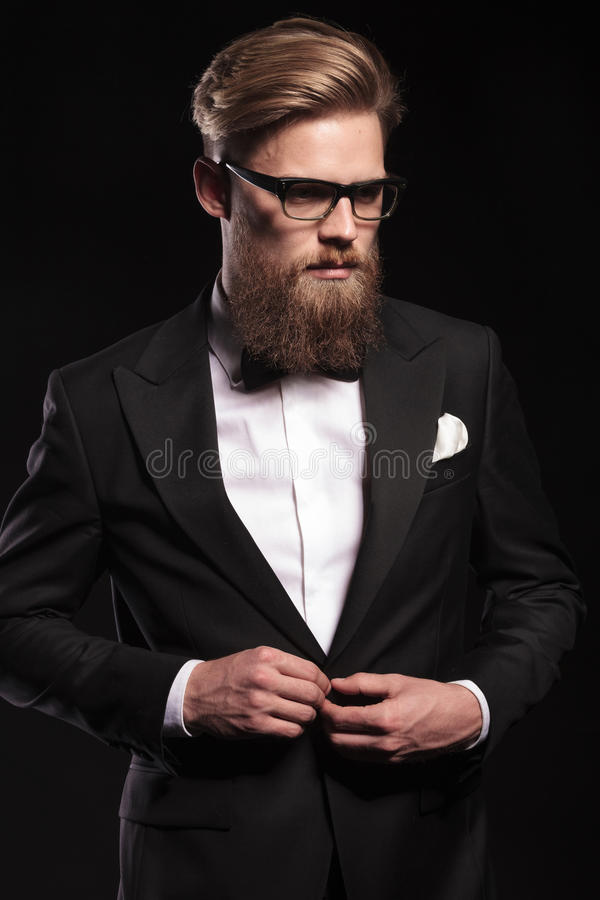 Business man looking down while closing his jacket. Picture of a elegant business man looking down while closing his jacket royalty free stock images