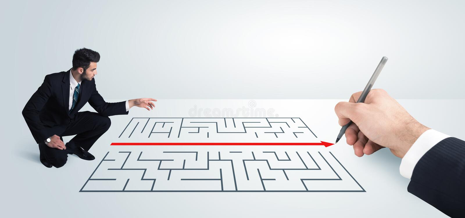 Business man looking at hand drawing solution for maze. Solution concept stock photography