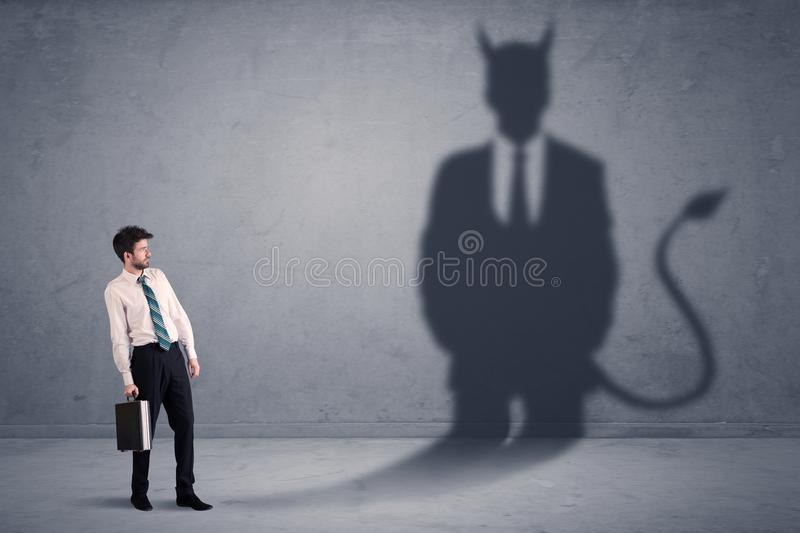 Business man looking at his own devil demon shadow concept. Background royalty free stock photo