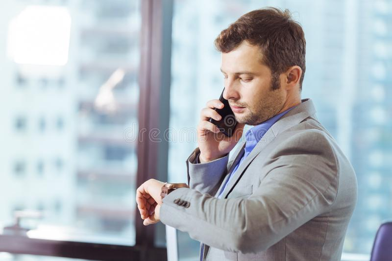Business man looking at his watch while calling phonecall stock photos