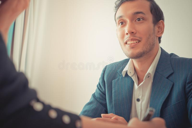 Business man looking interested while dealing with partner stock photography