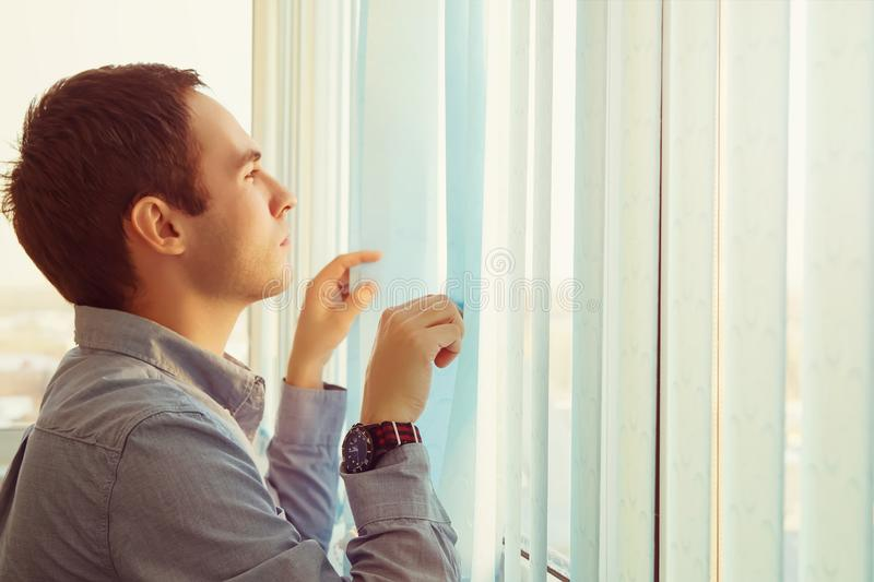 Business man looking out of window through the blinds. royalty free stock images