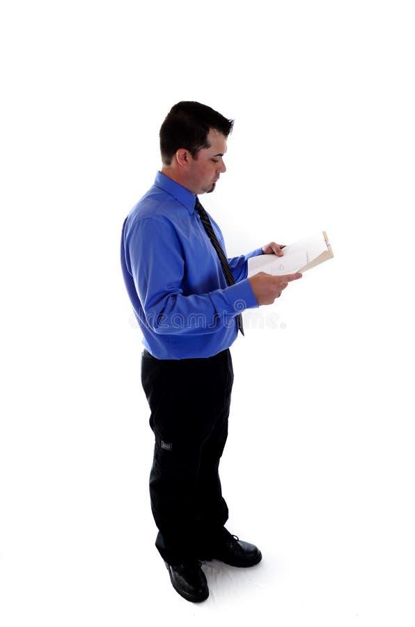 Business man looking at paperwork. A business man in blue shirt and tie looking at paperwork stock photos