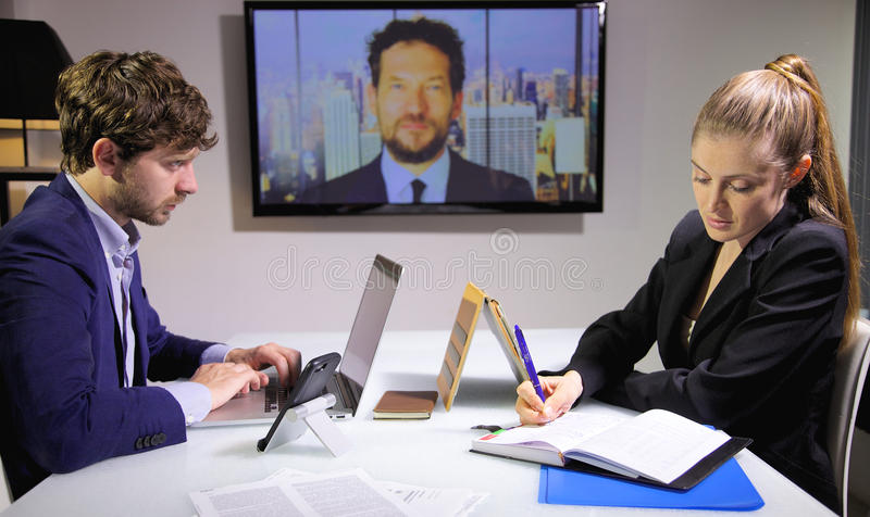 Business man looking partner writing while boss is looking in conference call. Business men and women talking with boss in conference call royalty free stock image