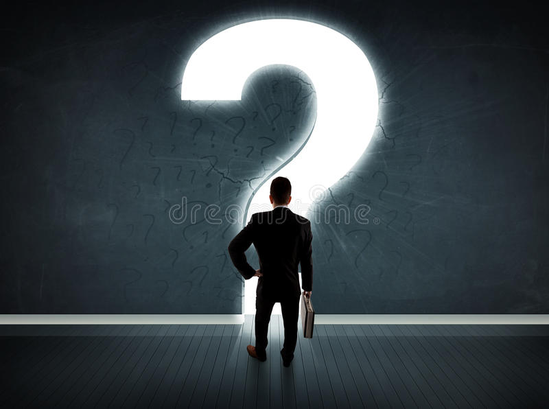 Business man looking at wall with a bright question mark stock image