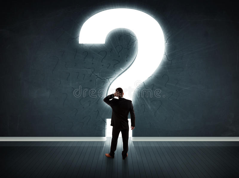 Business man looking at wall with a bright question mark royalty free stock image