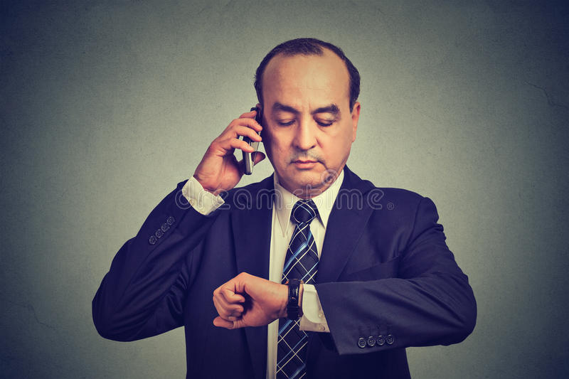 Business man looking at wrist watch, talking on mobile phone running late for meeting. Time is money. Business and time management concept. Middle aged business stock photos