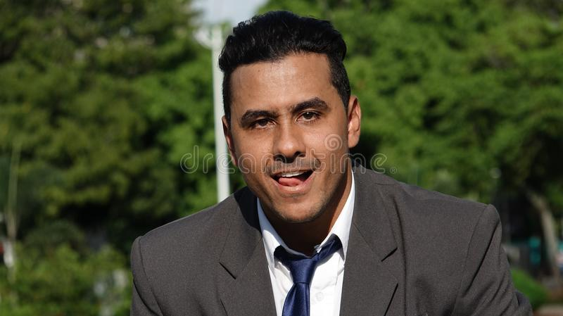 Business Man Making Funny Faces. A handsome young hispanic man stock images