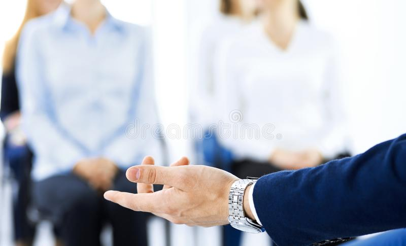 Business man making presentation to group of people. Speaker delivering a seminar to his colleagues or business training. Teamwork and coaching concept stock photo