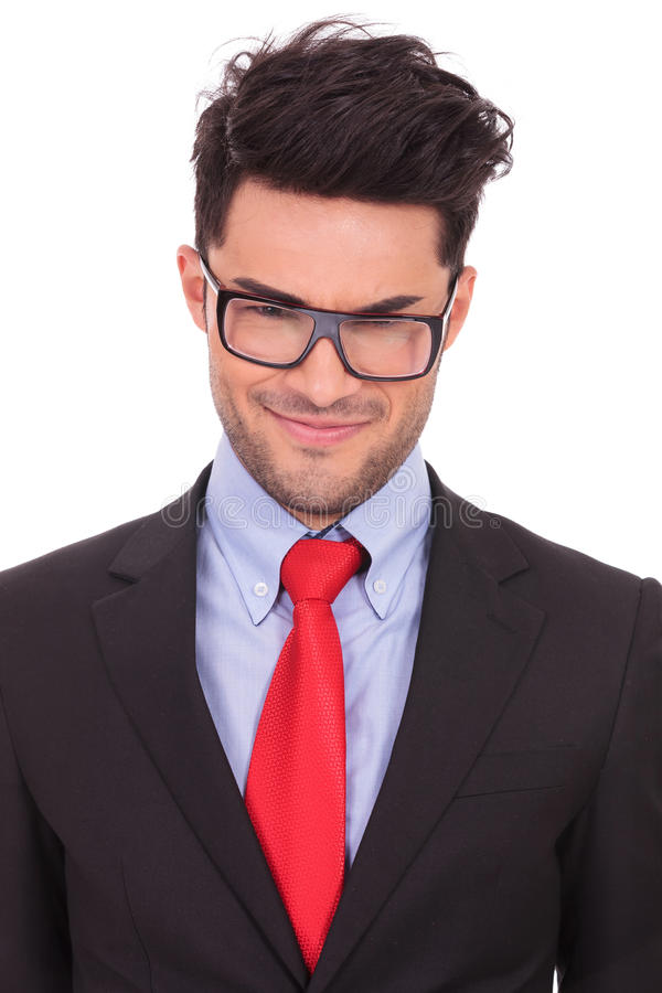 Business man with a malitious look. Closeup portrait of a young business man looking at the camera with a malitious look on his face, on a white background royalty free stock photos