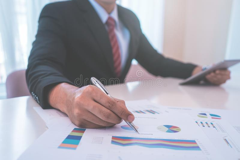 Business man marking on data using metal pen royalty free stock photos