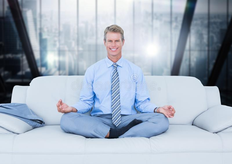Business man meditating on couch against blurry dark blue window. Digital composite of Business man meditating on couch against blurry dark blue window stock photo