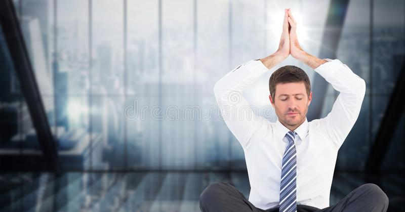 Business man meditating with hands over head against dark blue blurry window. Digital composite of Business man meditating with hands over head against dark blue royalty free stock image