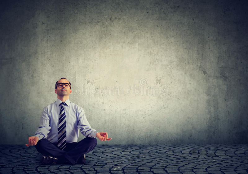 Business man meditating relaxing with eyes closed stock photography