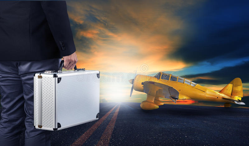 Business man with metal strong luggage standing in airport runways with yellow old yellow propeller plane use for air transport. And people traveling theme royalty free stock photos