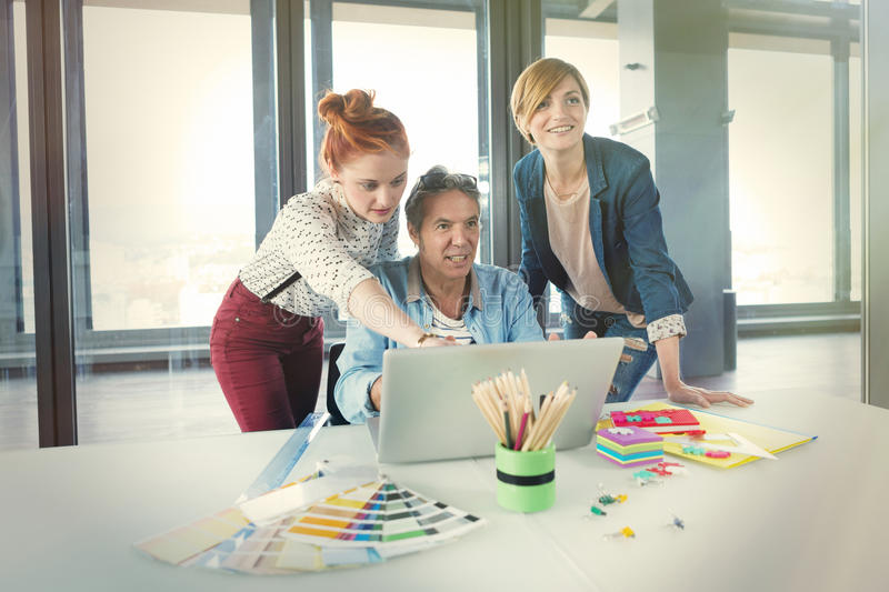 Business man in modern office showing his young female colleagues project on the laptop. Business men in modern office showing his young female colleagues stock photography