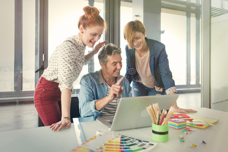 Business man in modern office showing his young female colleagues project on the laptop. Business men in modern office showing his young female colleagues royalty free stock photo