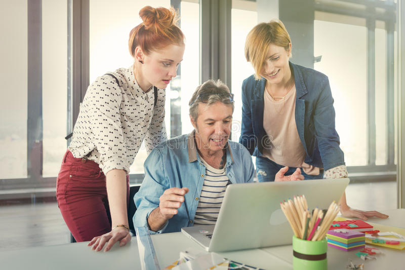 Business man in modern office showing his young female colleagues project on the laptop. Business men in modern office showing his young female colleagues stock image