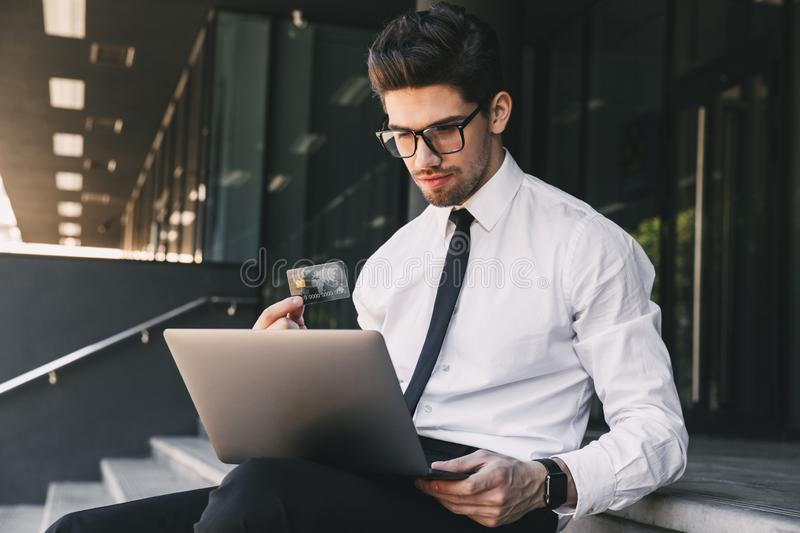 Business man near business center using laptop computer holding credit card. Image of handsome business man near business center using laptop computer holding stock photography