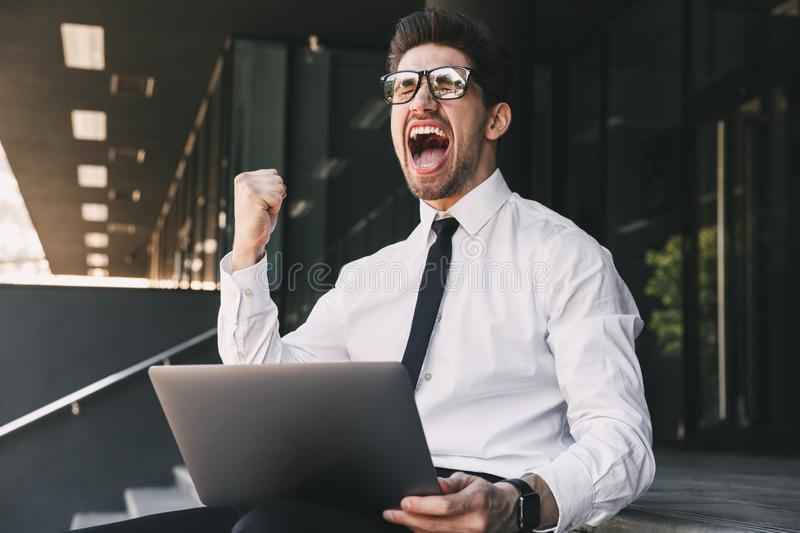 Business man near business center using laptop computer make winner gesture. Image of handsome shocked business man near business center using laptop computer stock photography