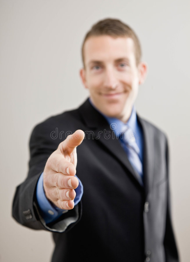 Business man offers hand to shake. Confident businessman offering hand for handshake stock photo